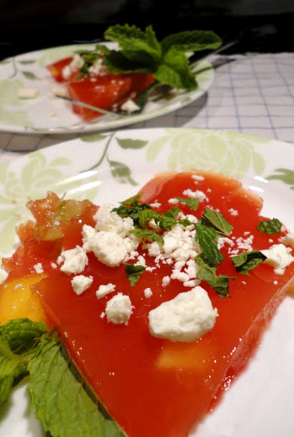 Watermelon Jello salad with feta and mint is a delicious summer side salad recipe. Fresh fruit is added to homemade watermelon Jello and then topped with fresh mint and feta cheese. This watermelon Jello salad recipe makes a perfect light dessert, too.