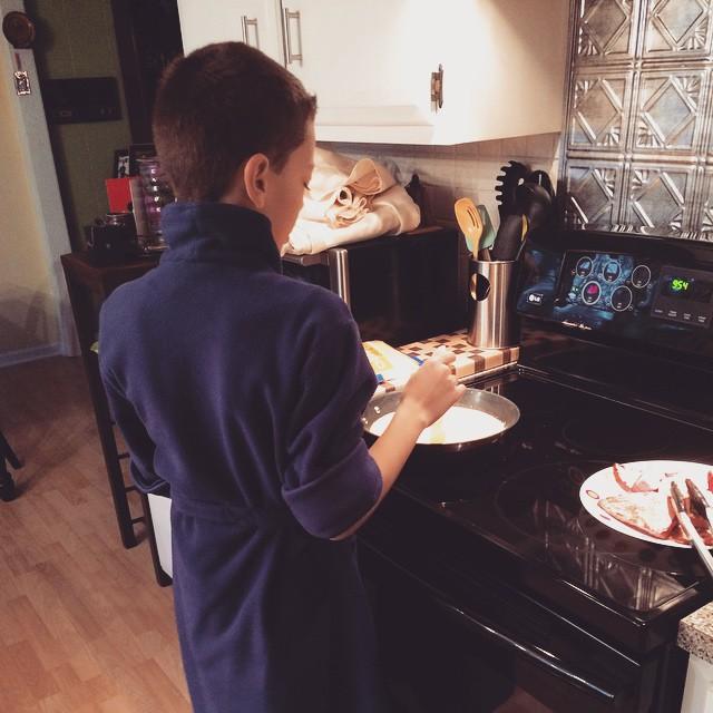 Jacob is scrambling some eggs. In his robe of course :) #kidscook #kidsinthekitchen