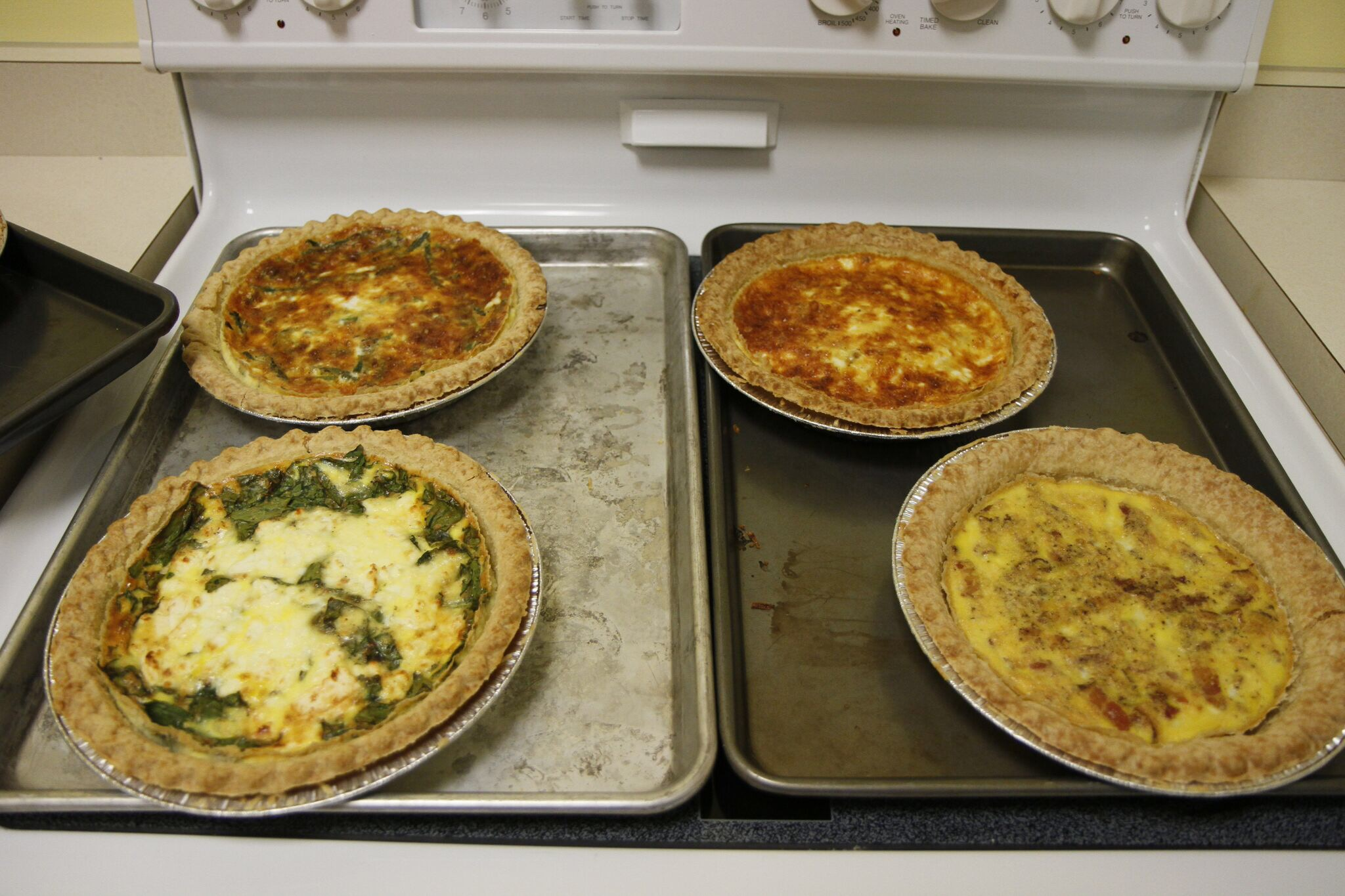 4 delicious quiche recipes: spinach feta, bacon quiche, a ham and cheddar quiche,; egg only quiche, and egg and cheddar, with peppers, onions, and zucchini