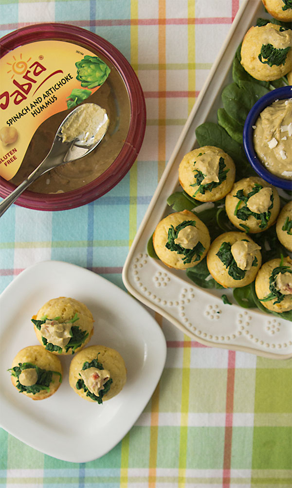 Spinach Artichoke Hummus Corn Muffins, topped with sauteed garlic-spinach and a dollop of Sabra spinach artichoke hummus | gluten free | healthy appetizer | sponsored by @sabra
