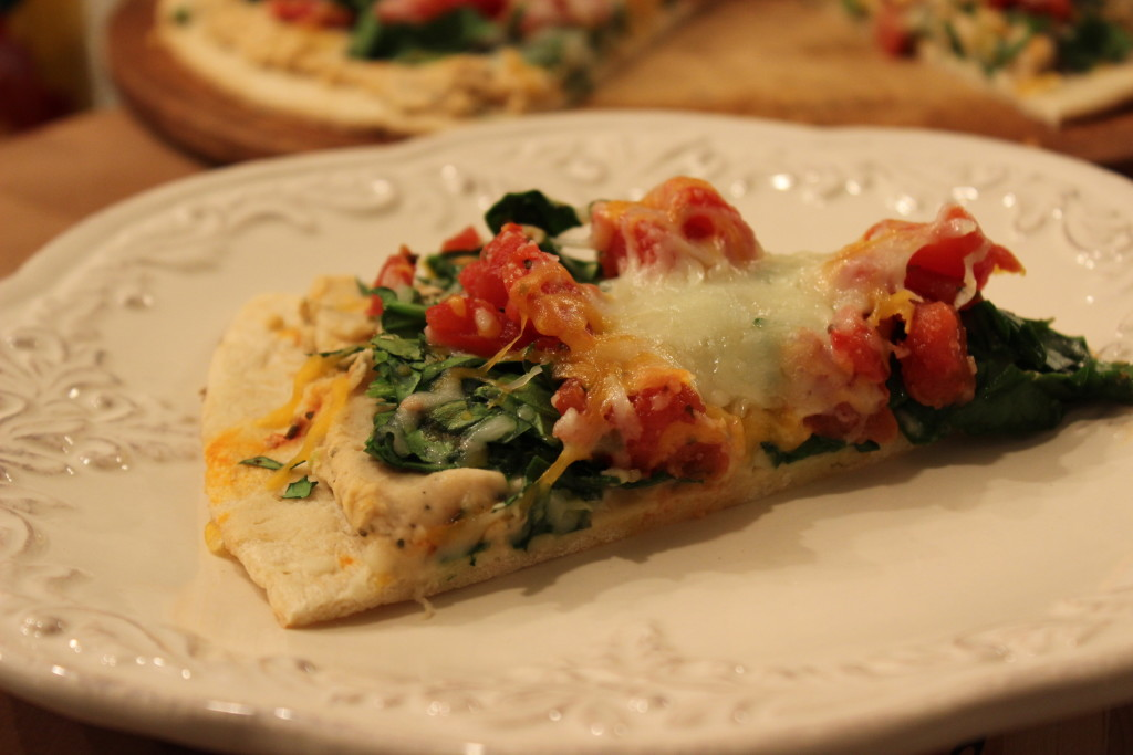 Hummus Pizza: Classic hummus topped with spinach, diced tomatoes and mozzarella cheese.