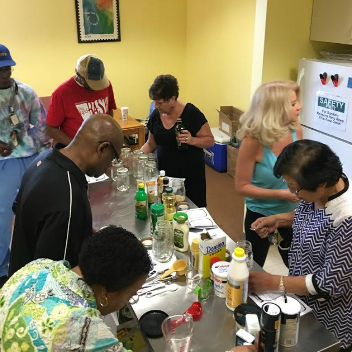Clients at the Little Red Door Cancer Agency make Mason jar salad dressings in a Door to Wellness workshop.