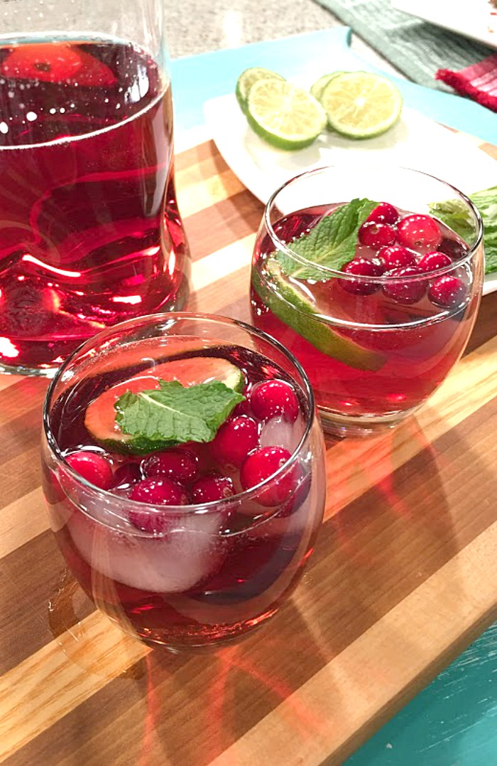 Sparkling iced tea is a delicious way to serve iced tea for holiday events. This drink is bursting with fresh cranberries and mint, helping to deck the halls with red and green color! | Recipe on basilmomma.com